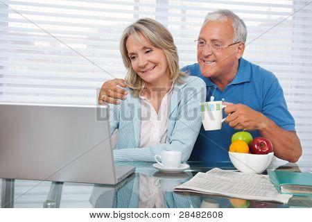Pareja feliz usando laptop desayunando