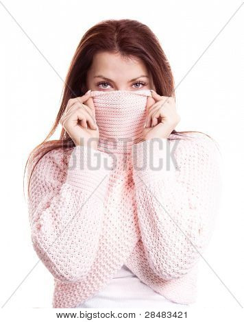 displeased young woman wearing a high neck sweater, isolated against white background