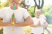 Mature Man With Chakra Points Practicing Zen Yoga In Group Outdoors poster