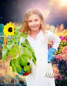 Beatifull girl with sunflower in the garden at summer day. Child relaxing in garden in sunny day. Li poster