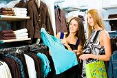 stock photo of shopping center  - Photo of two girls in the clothing store holding a blue dress and looking at it with smiles on the background of different clothes - JPG