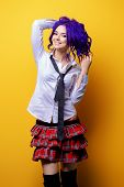 Portrait of a student girl with purple hair in white blouse and checkered skirt posing on yellow bac poster