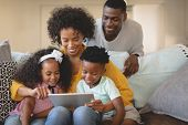Front view of African American mother with her children using digital tablet on sofa while father lo poster