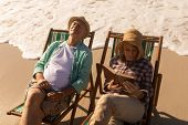 Front view of active senior woman reading a book while senior man relaxing on sun lounger at beach poster