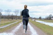 Fit Muscular Woman Jogging Away From Camera Along A Wet Country Dirt Road In Winter In A Concept Of  poster