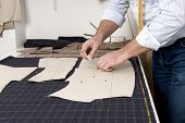 picture of tailoring  - Tailor at work drawing line on fabric with chalk - JPG