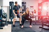 Sport, Fitness, Teamwork, Weightlifting And People Concept - Young Woman And Personal Trainer With B poster