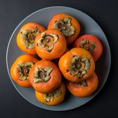 Delicious Fresh Persimmon Fruits On Black Background. poster