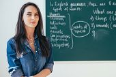 Smiling Female Teacher Standing In Front Of Blackboard In Classroom poster