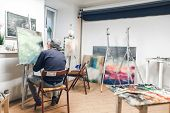 Talented Artist Sits On A Chair In A Cozy Artistic Studio And Paints An Oil Painting. Creative Atmos poster