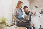 A Young Girl Works At A Laptop While Sitting. Bearded Man Helps In The Work Of A Smiling Young Girl  poster