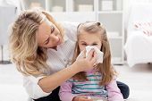 stock photo of blowing nose  - Woman at home blowing the nose of her little girl - JPG