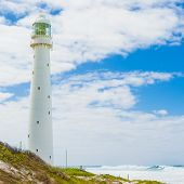 Lighthouse On A Rugged Coastline During The Daytime poster