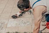 A Circular Saw. A Man Sawing Ceramic Tiles. Worker Sawing A Tile On A Circular Saw. Selective Focus poster