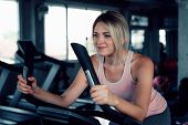 Portrait Of Attractive Woman Is Workout Cycling Exercise In Fitness Gym., Portrait Of Pretty Caucasi poster