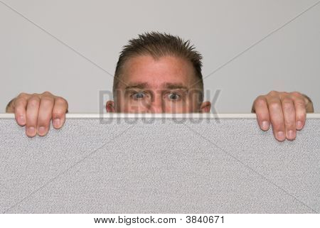 Man Peering Over Office Cubicle