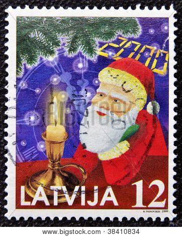 LATVIA - CIRCA 1999: A christmas stamp printed in Latvia shows papa noel santa claus circa 1999