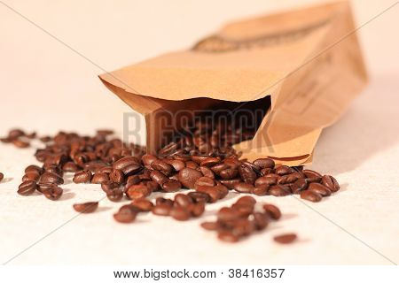 Coffee beans overflowing from paper bag on traditional sack textile