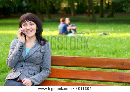 Happy Woman Talking On Mobile Phone In Park