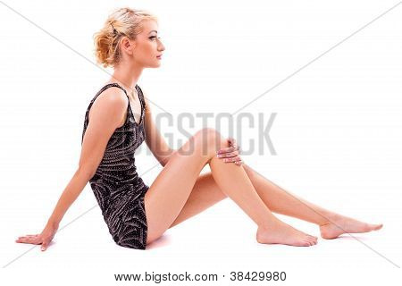 Young Blond Woman Sitting On The Floor Isolated On White Background