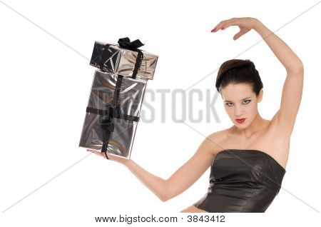 Beautiful Woman In Black Leather Corset Balancing With Two Silver Christmas Presents