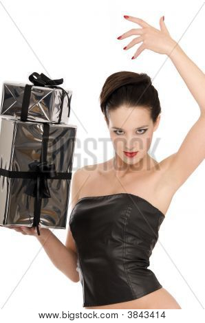 Young Woman In Black Leather Corset Holding Two Silver Christmas Presents