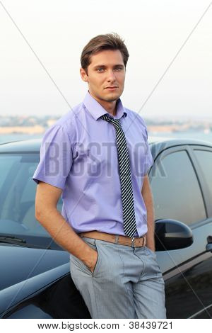 A Young Businessman Man On The Background Of Cars, Outdoors