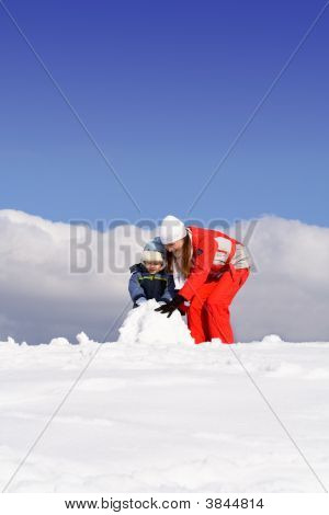 Mother With Kid Making Snowman