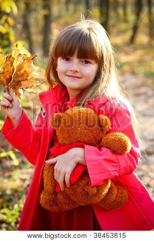 Smiling Girl With Maple Leaves And Teddy Bear