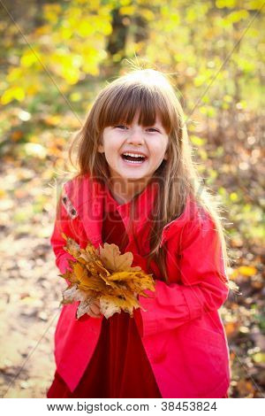 Portrait Of A Laughing Girl In The Autumn Forest With Maple Leaves