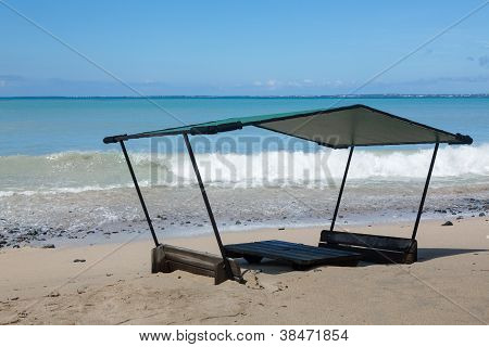 Seats And Table On Beach Covered In Sand