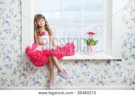 Romantic Dreaming Young Girl Sitting On Windowsill Near Flower