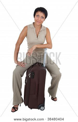 Young Tourist Woman Sits On The  Brown Traveling Suitcase Isolated