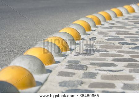 Curb Separated Asphalt Road And Cobblestone