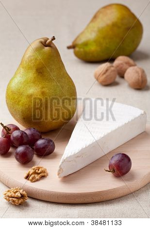 Green Pears, Cheese Brie, Walnuts And Grapes On Wooden Board