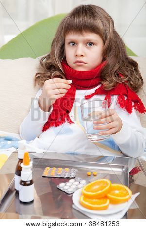 Little Sick Girl With Scarf In Bed Is Taking Medicine