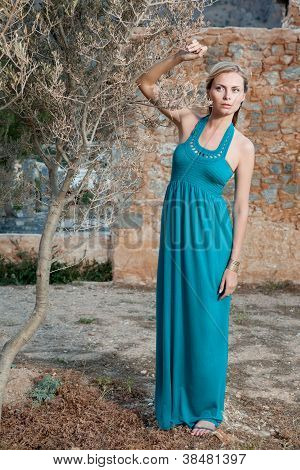 Portrait Romantic Young Blond Woman In Blue Near Olive Tree