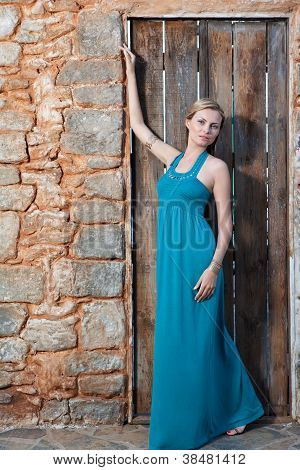 Romantic Young Blond Woman In Blue On Stone Wall Background