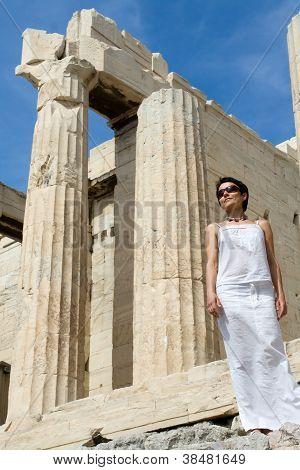 Mujer cerca de Propileos columnas Acrópolis Atenas Grecia sobre fondo de cielo