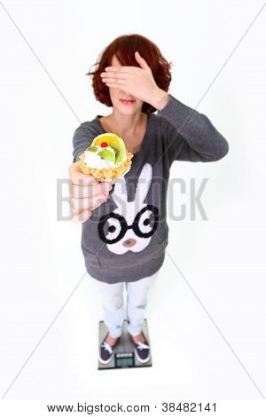 Girl Standing On The Weigher, Holding A Cake And Shutting Her Eyes Isolated On White Background