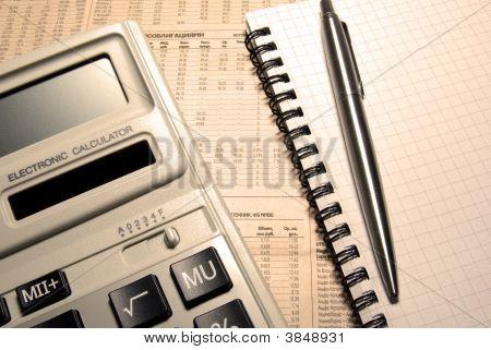 Calculadora, pluma, cuaderno y periódico. Concepto financiero.