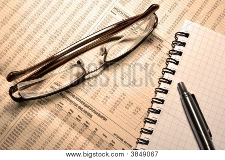 Glasses, Pen And Notebook Laying On Newspaper With Financial Numeric Data. Photofilter.