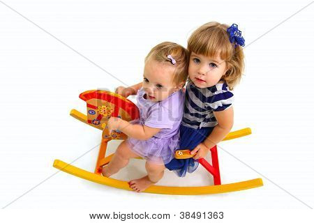 Two Cute Babies Riding On A Toy Wooden Horse Isolated On White B