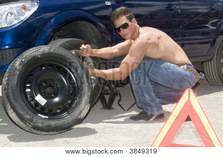 Man Changing A Wheel Of His Car