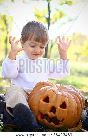 Portrait Of An Enthusiastic Little Boy With Halloween Pumpkin