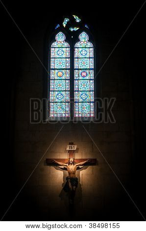 Crucifix In Church Under Stained Glass Window.