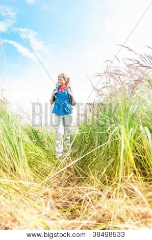 Young Girl Walking In Meadow With Backpack On.