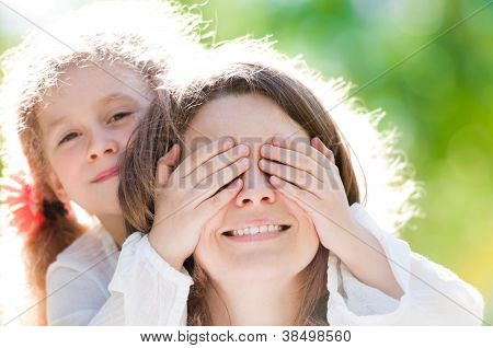 Beautiful Little Girl With Hand On Eyes Of Mother