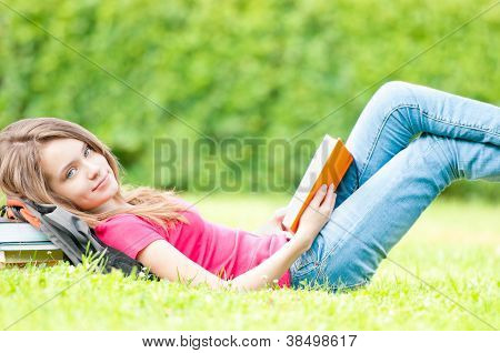 Happy Student Girl Lying On Grass With Opened Book