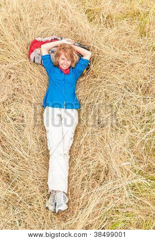 Laughing Woman Lying Down On Grass In Meadow.